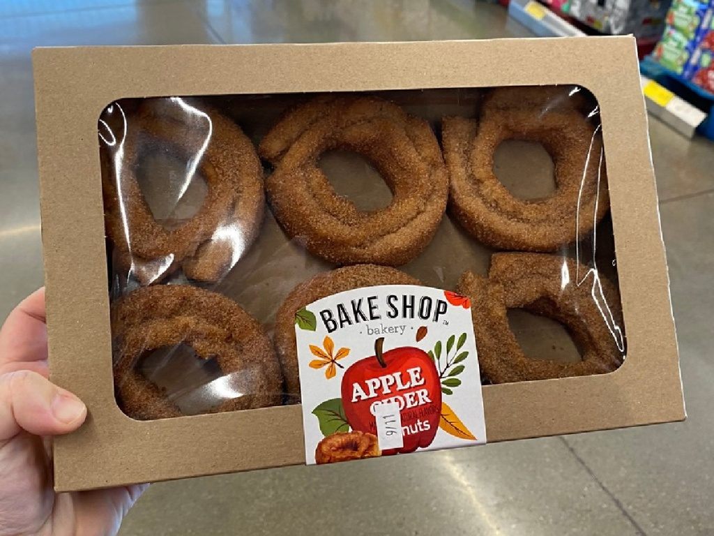 """hand holding box of donuts that say """"apple cider"""" on them"""