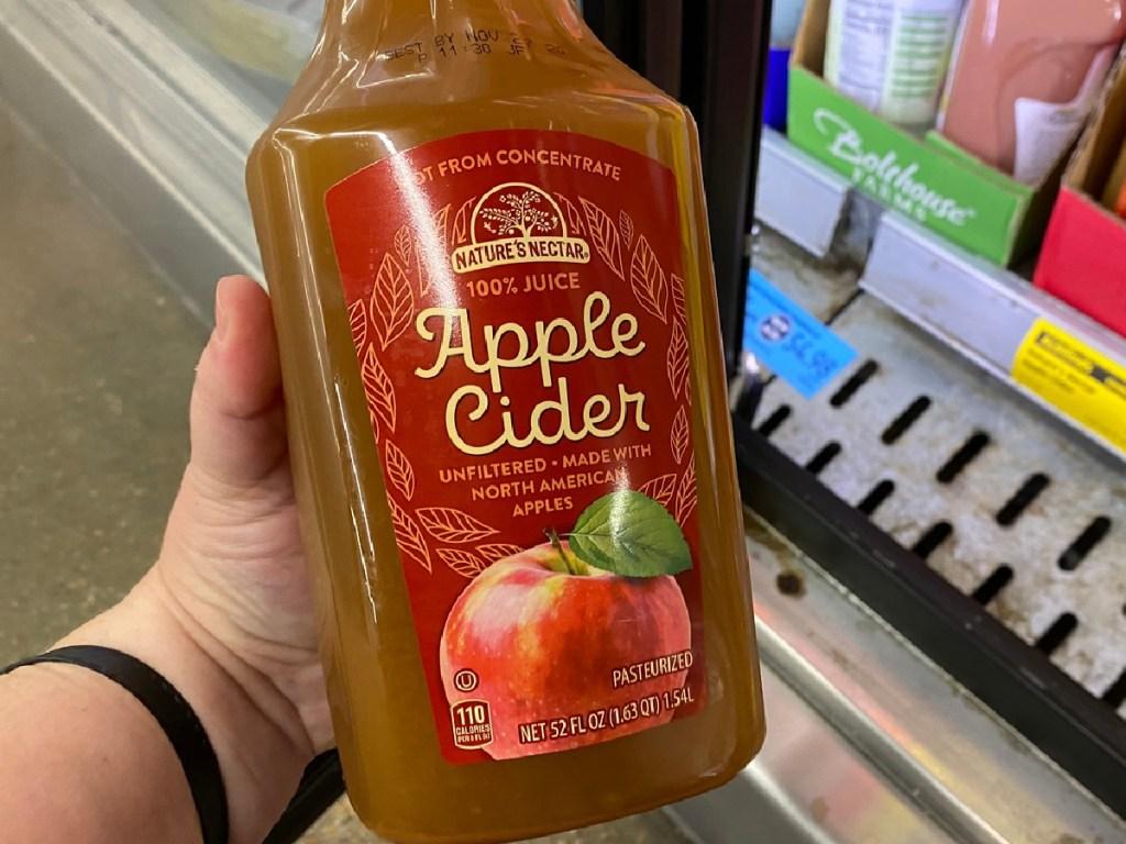 hand holding plastic bottle of apple cider near store freezer