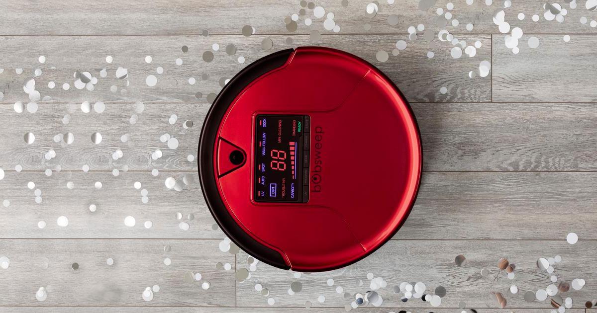 red robotic vacuum cleaning glitter off floor