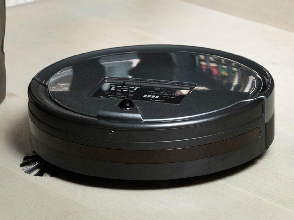 Black robotic vacuum on hard floor