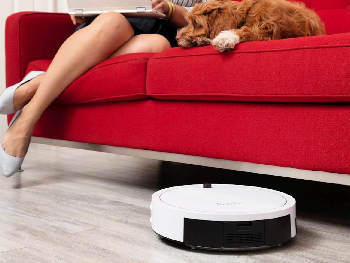 robotic vacuum going under large red sofa