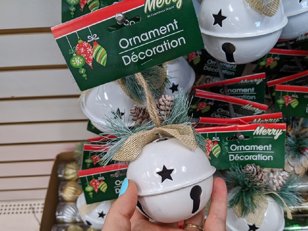 hand holding white bell ornament in store