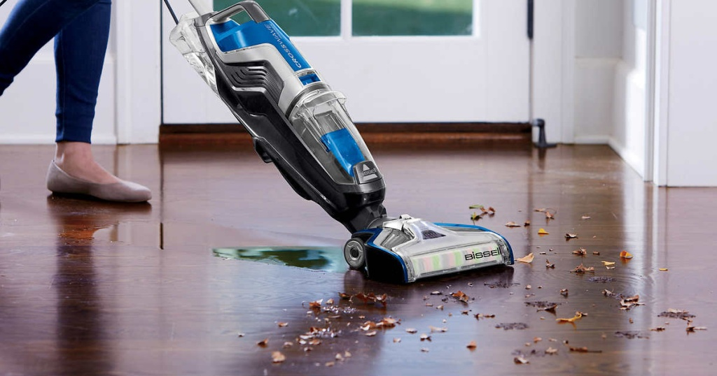 person pushing vacuum cleaner over wood floor mess