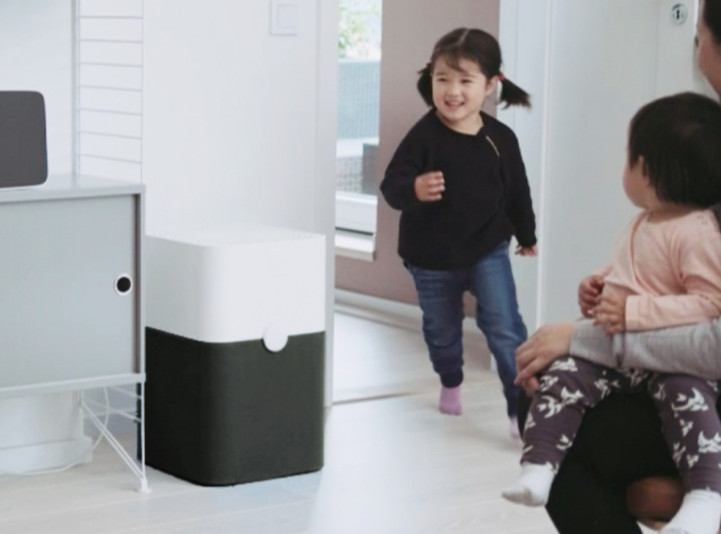 girl running around with white and black blueair air purifier on floor