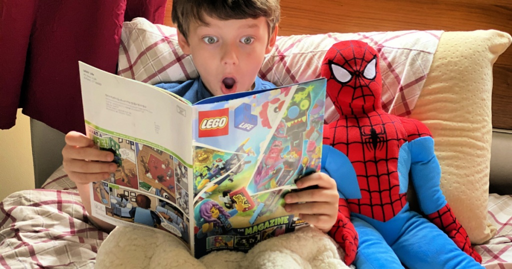boy reading a lego magazine on his bed with spiderman plush
