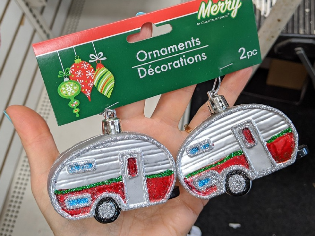hand holding 2 little ornaments shaped like campers