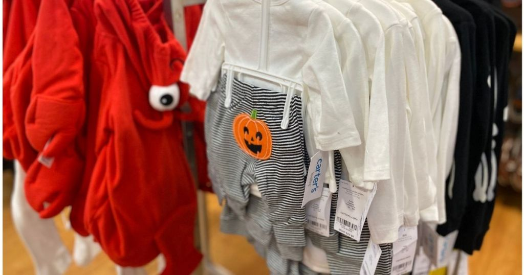 pumpkin and striped pants baby set hanging in store