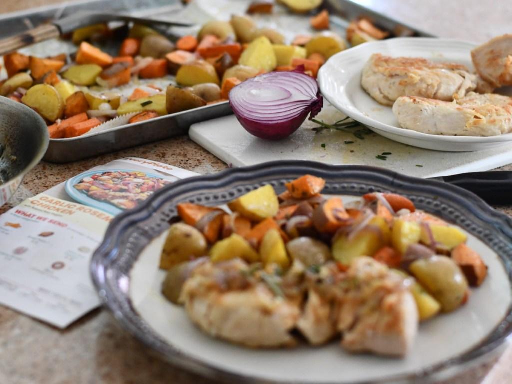 chicken dinner on plate pan of vegetables