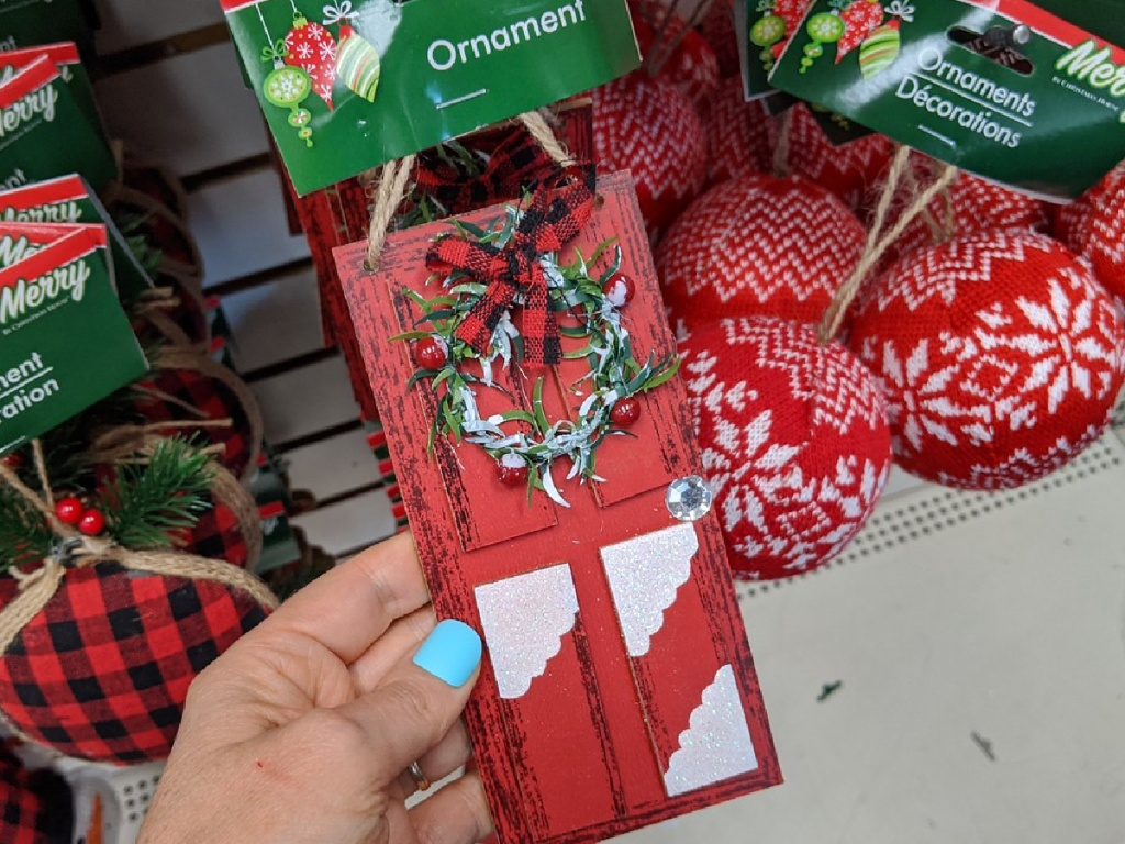hand holding ornament that looks like red Christmas door in store