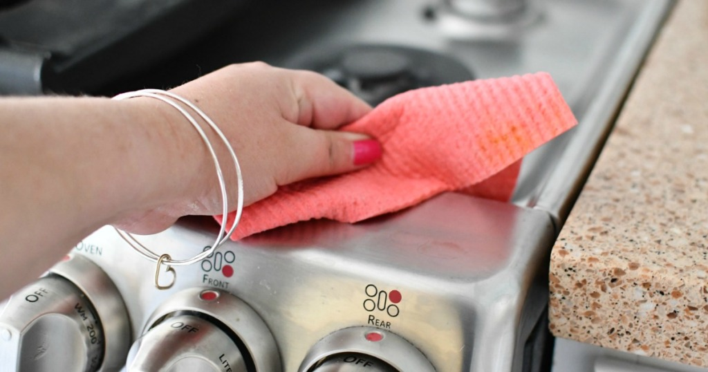 hand holding pink swedish dishcloth wiping stove top