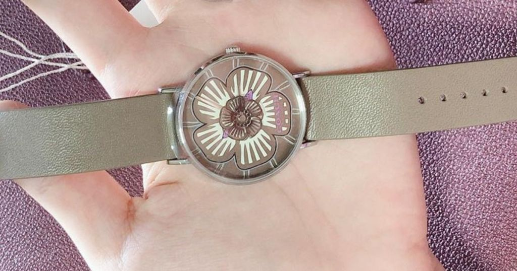 flower coach watch on hand with shiny purple background