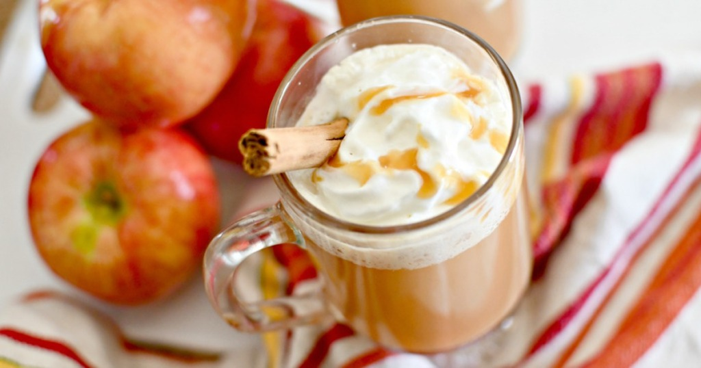 hot apple cider in glass cup with whipped cream and caramel sauce