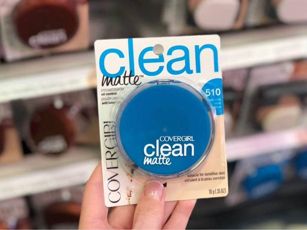 hand holding blue jar of face powder