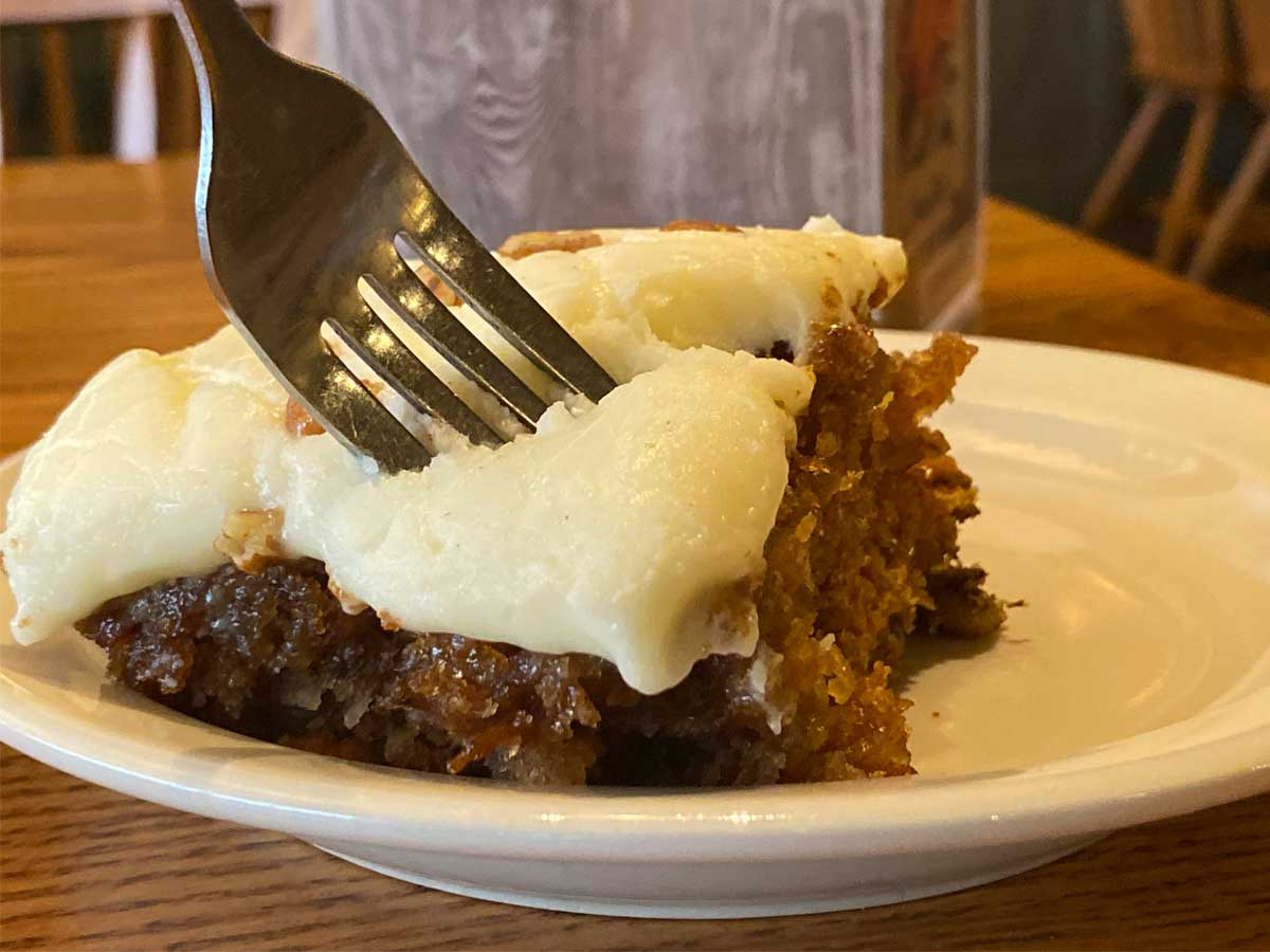 close up of a fork piercing a piece of carrot cake on a white plate