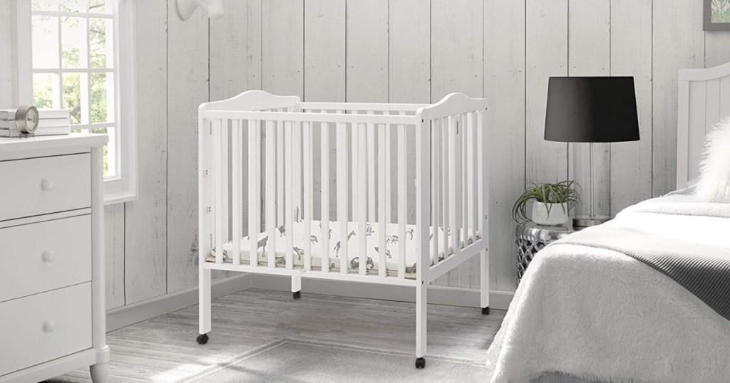 white delta mini crib in gray room