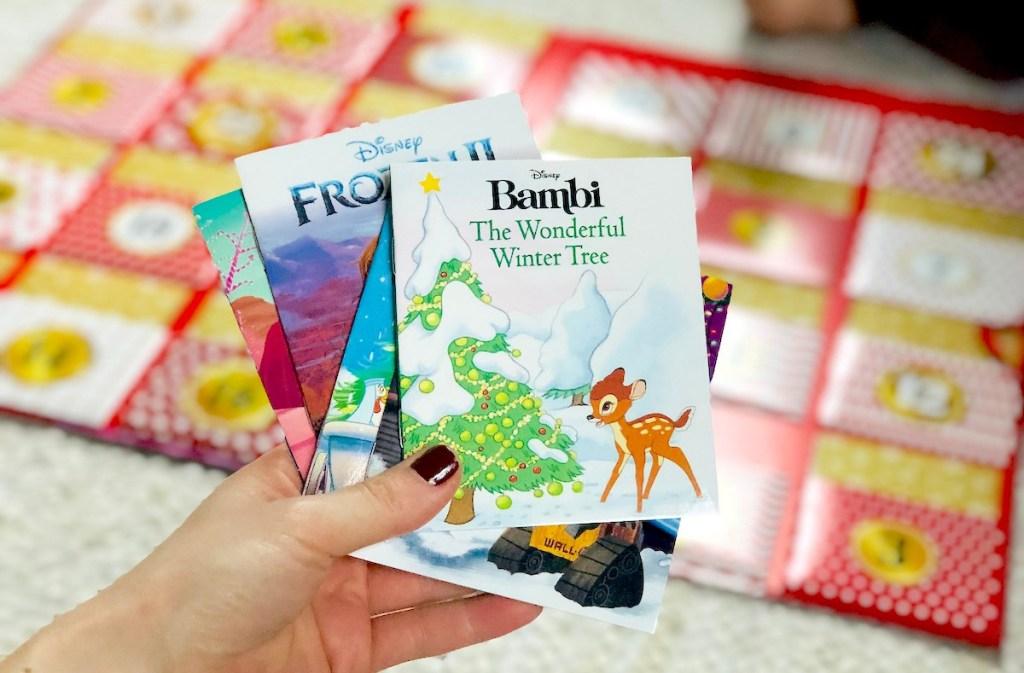hand holding multiple mini christmas books