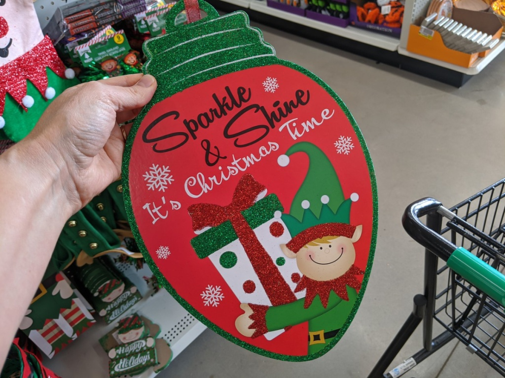 hand holding up sign that is shaped like an ornament with Christmas greetings written on it