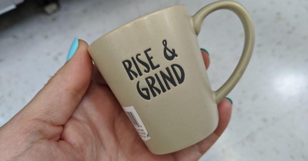 "hand holding tiny mug that says ""rise & grind"""