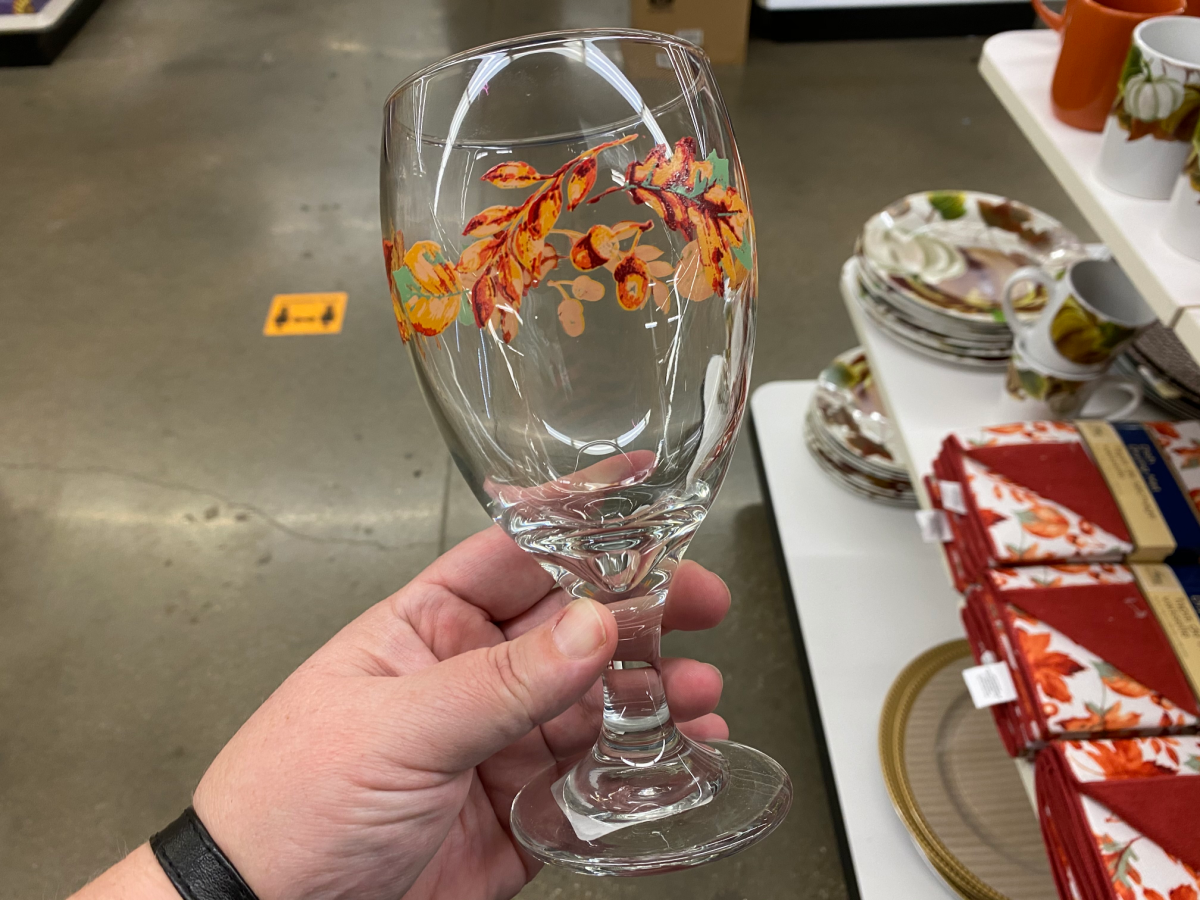hand holding glass with fall leaves painted on it