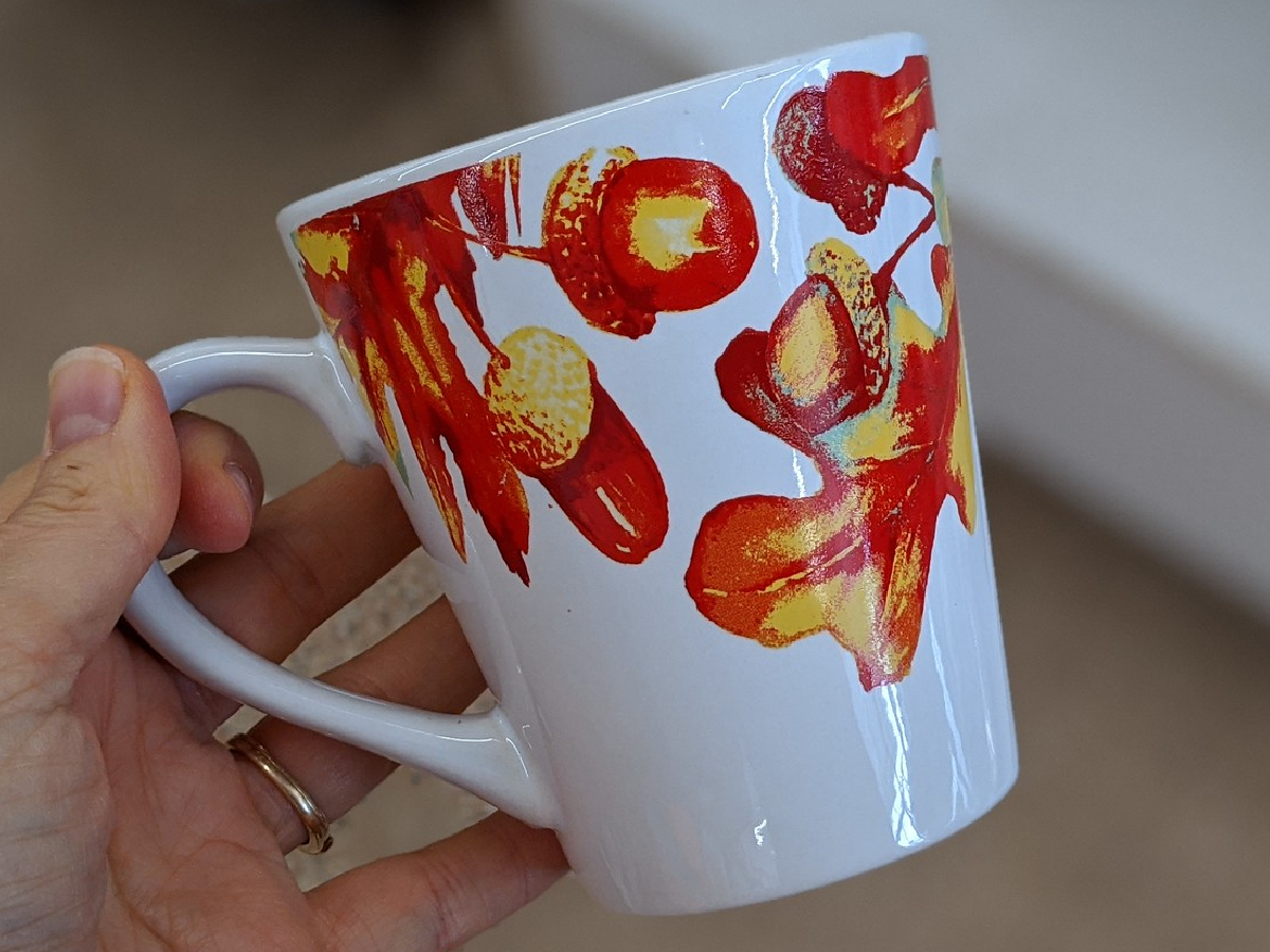 hand holding mug that has leaves painted on it