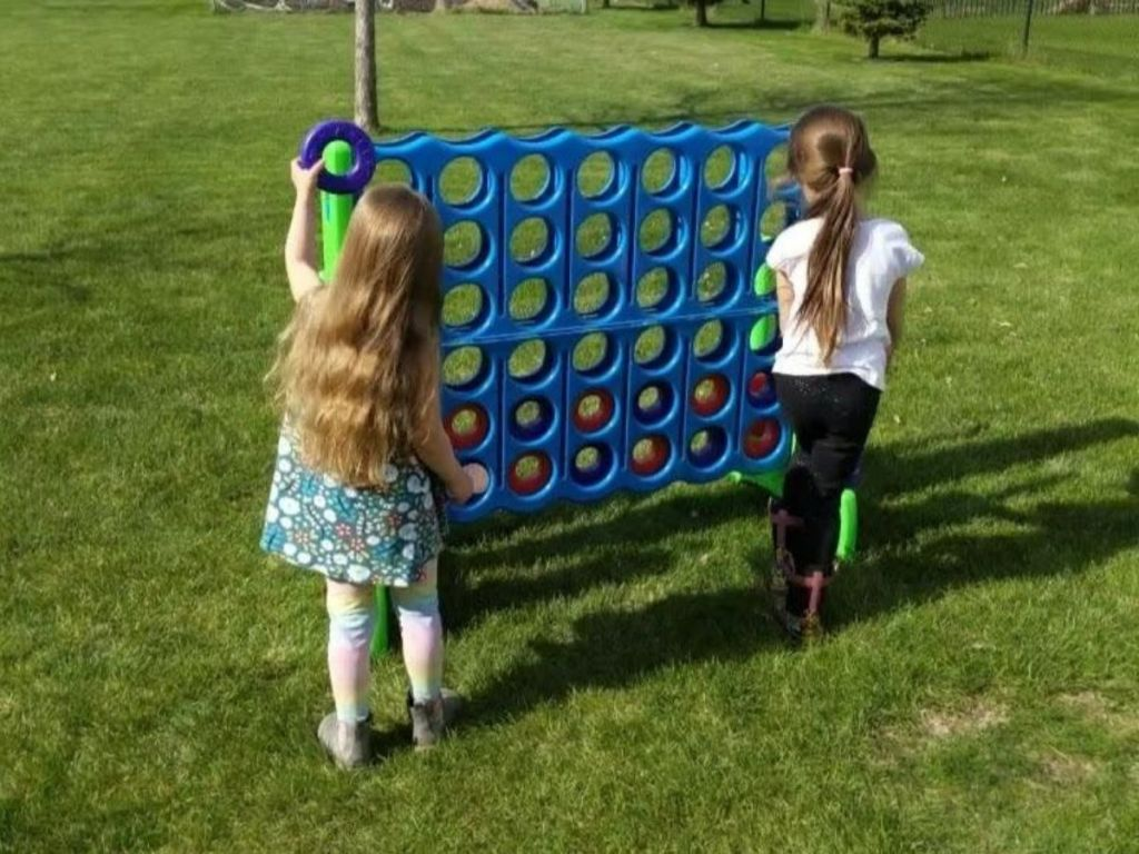 2 girls playing with giant blue connect 4 game