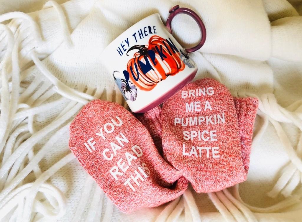 pumpkin mug and novelty socks on white tassel blanket