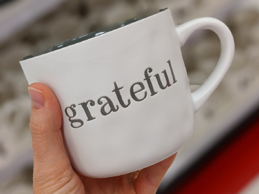 "hand holding mug that says ""grateful"" on it"