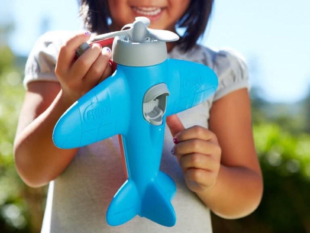 little girl holding blue airplane