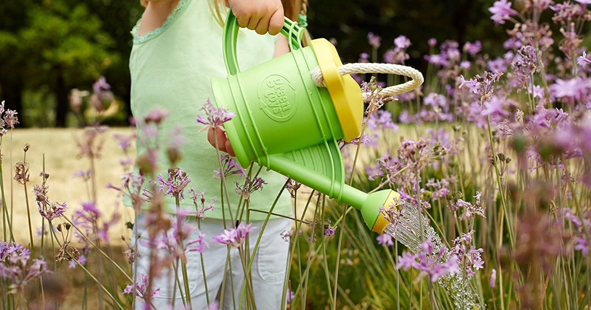 Girl outside pouring water on flowers from a green, Green Toys watering can