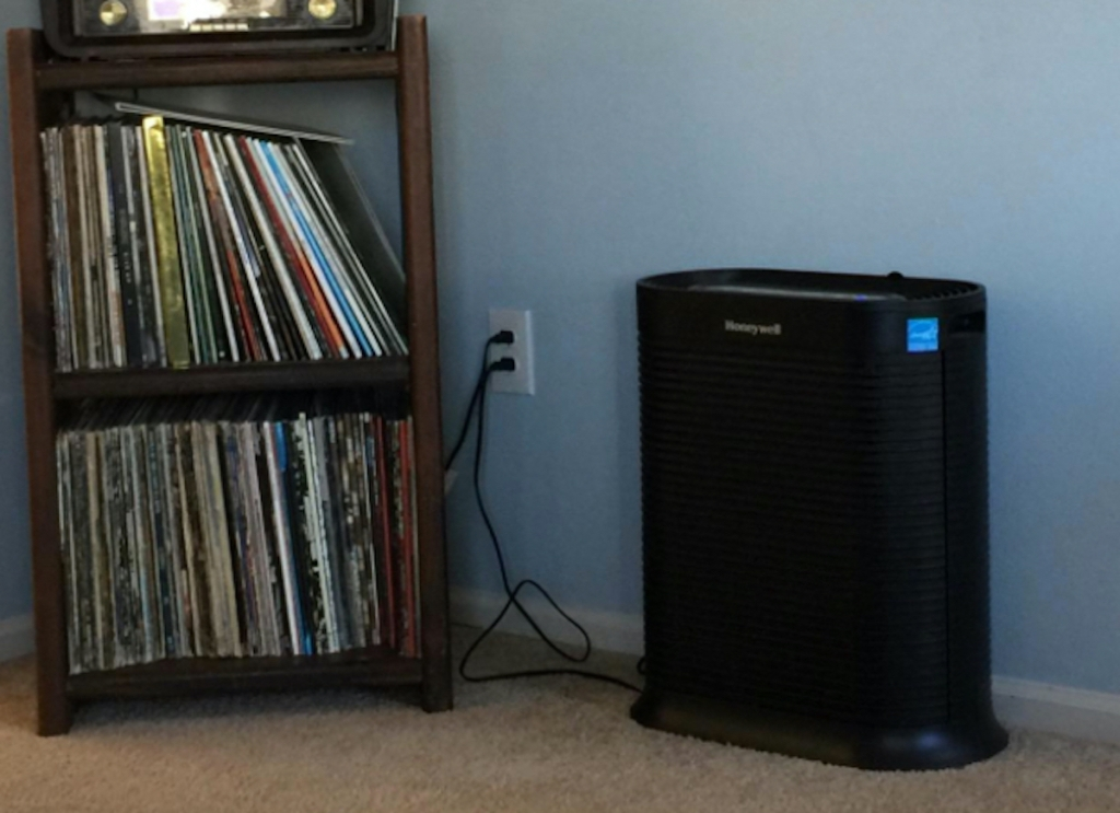 black honeywell air purifier sitting on floor next to shelves of vinyl records