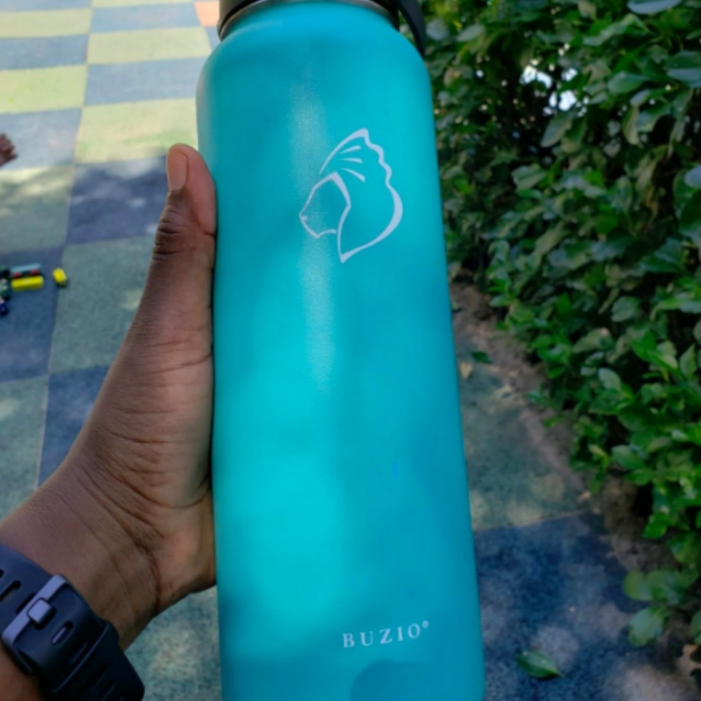 lady holding a teal blue water bottle outside