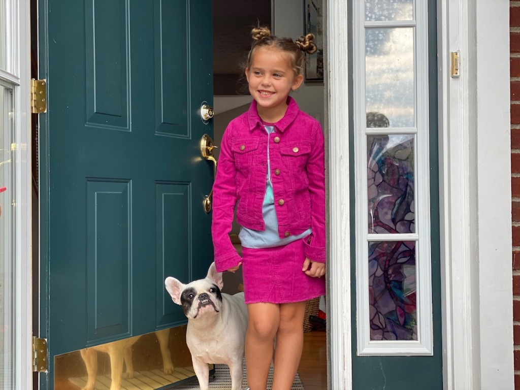 girl standing in jean jacket and skirt at front door with dog