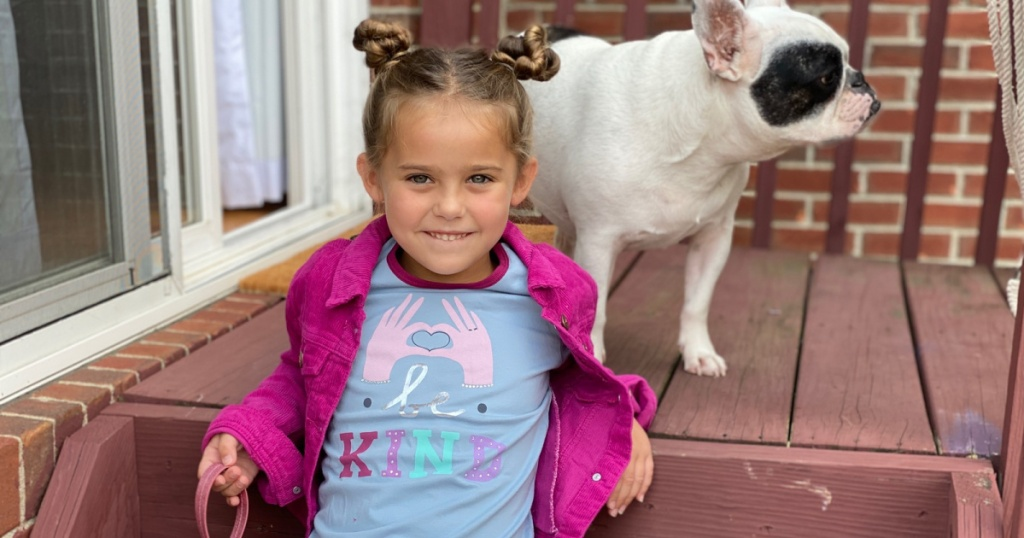 little girl on porch with dog wearing pink jacket