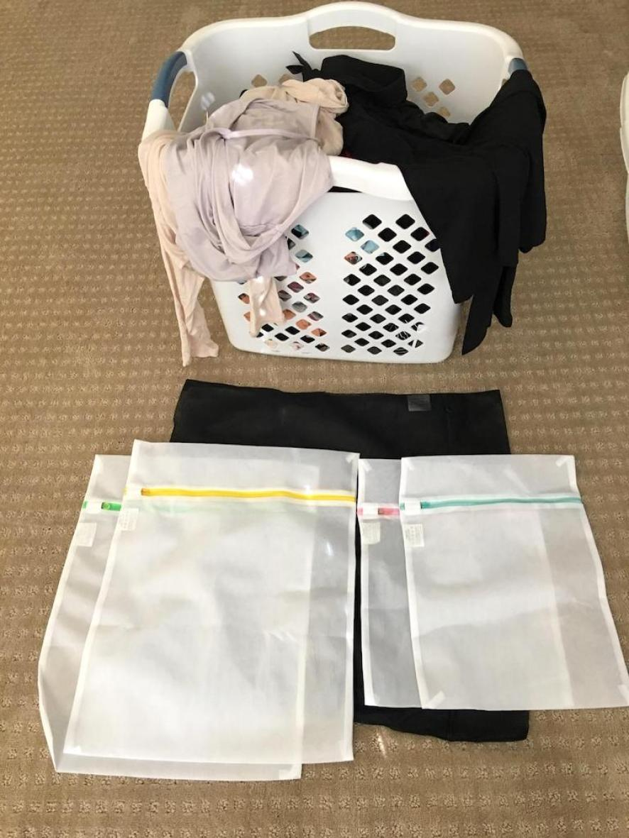 laundry basket on floor next to mesh laundry bags