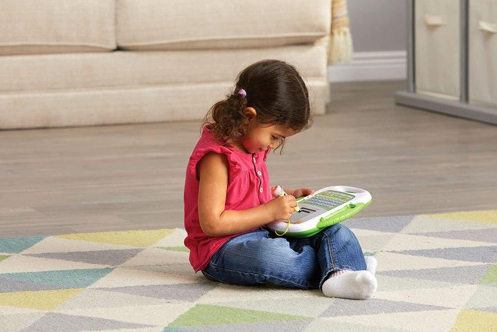 little girl sitting on floor using leapfrog mr scribble toy
