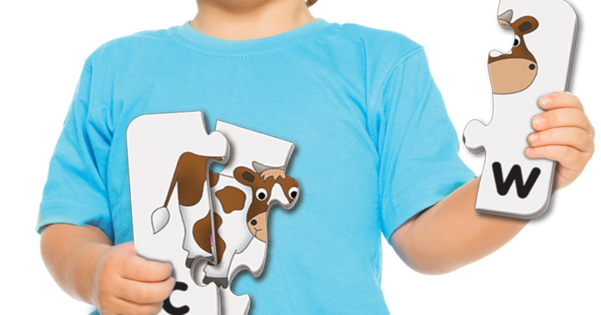 boy in blue t shirt holding matching game cards that are in three puzzle pieces which spell the word cow with a cow picture