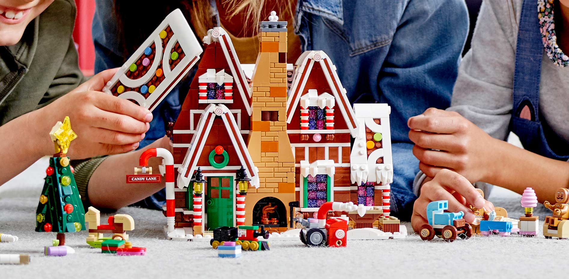 family playing with lego gingerbread house
