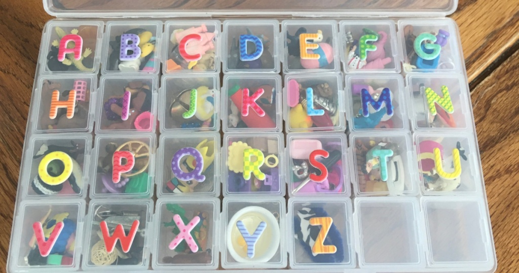 plastic box with letters on outside and little objects inside