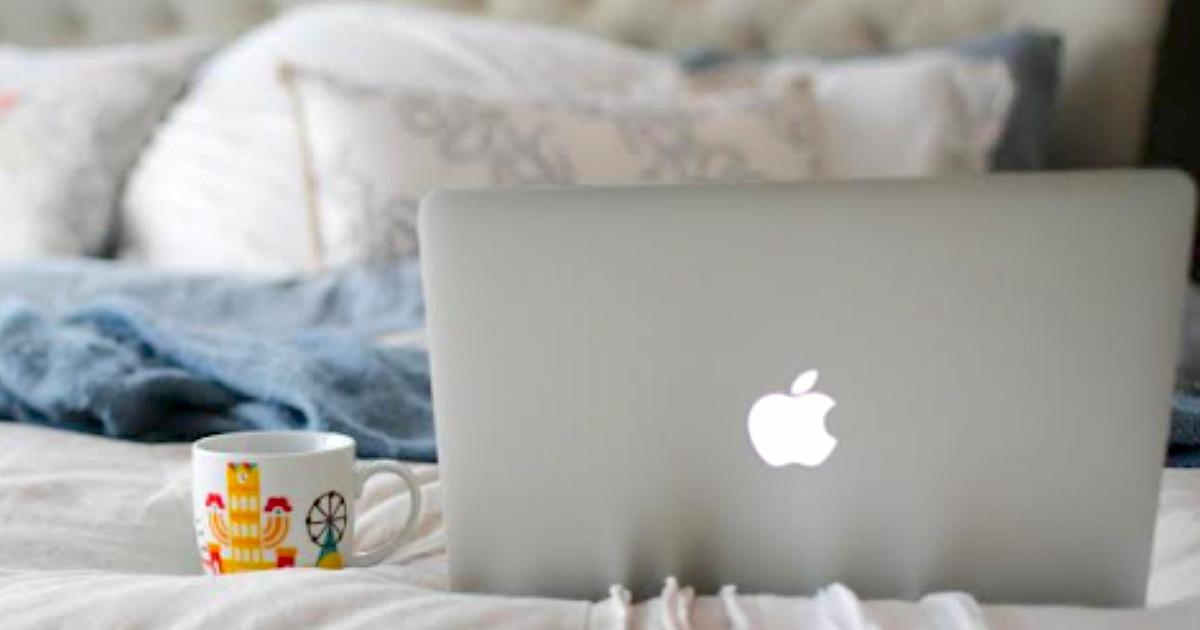 Macbook on bed with coffee mug