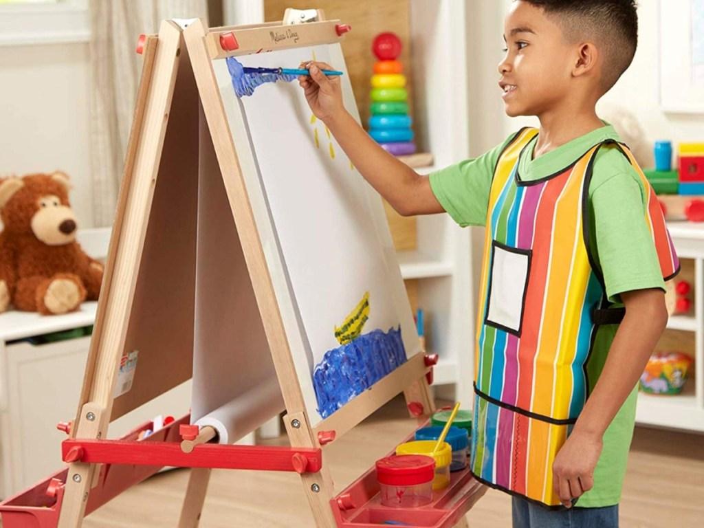 anak laki-laki melukis di atas kuda-kuda