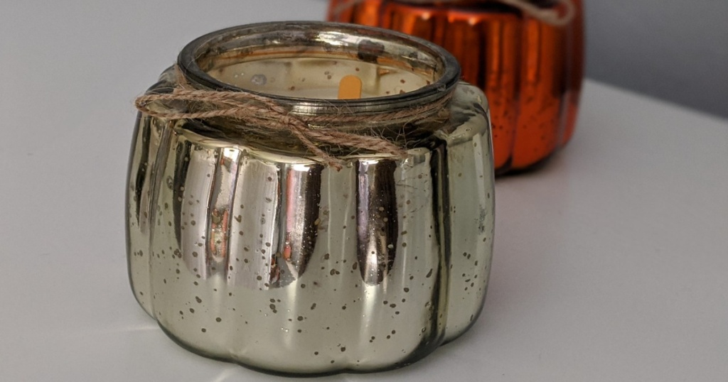 silver candle on table with orange one in background