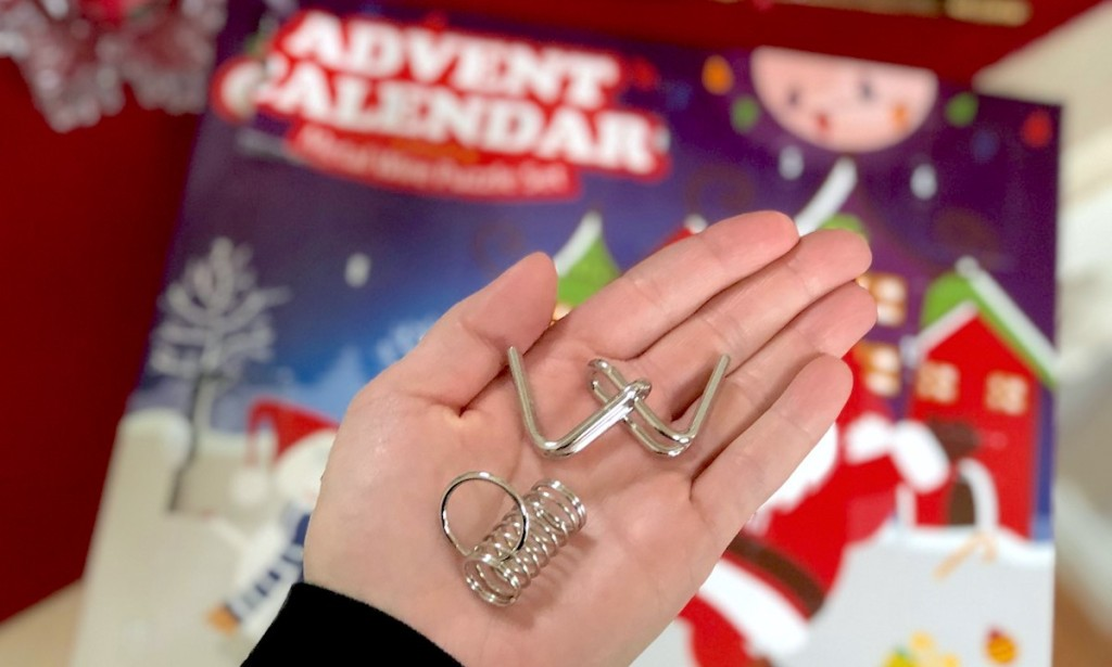 hand holding advent calendar metal puzzles