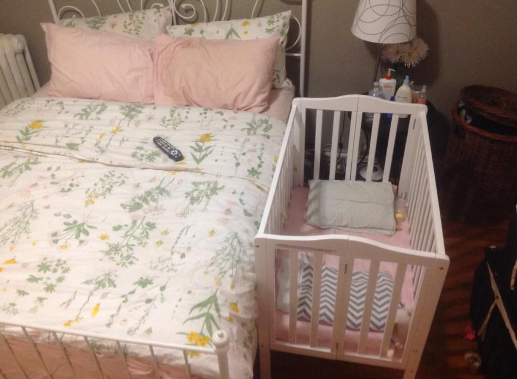 mini crib next to bed