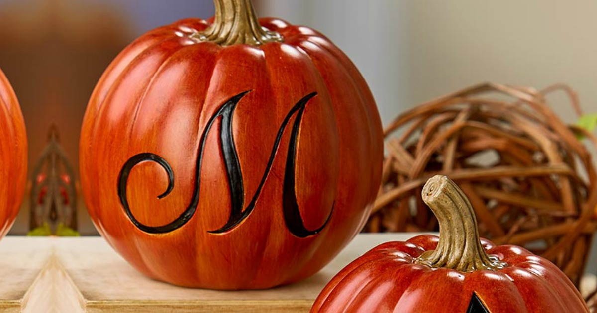 monogrammed decorative pumpkins on a wooden surface
