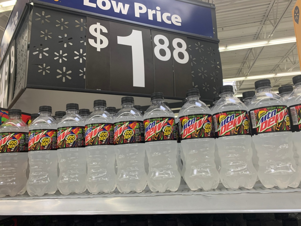 store price sign with bottles of soda under it