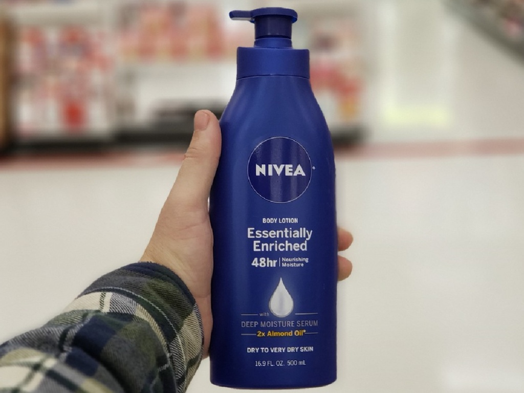 hand holding bottle of Nivea brand lotion in a store