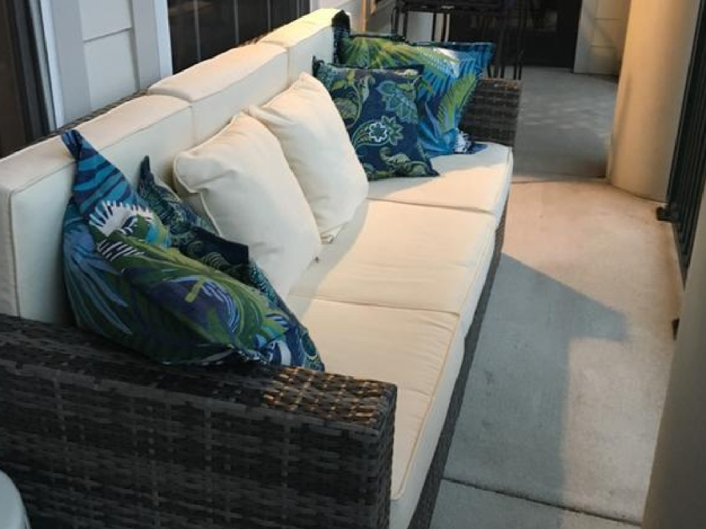 couch on porch with tan and teal pillows