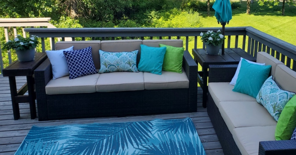 couches outdoors on patio with cushions and a rug