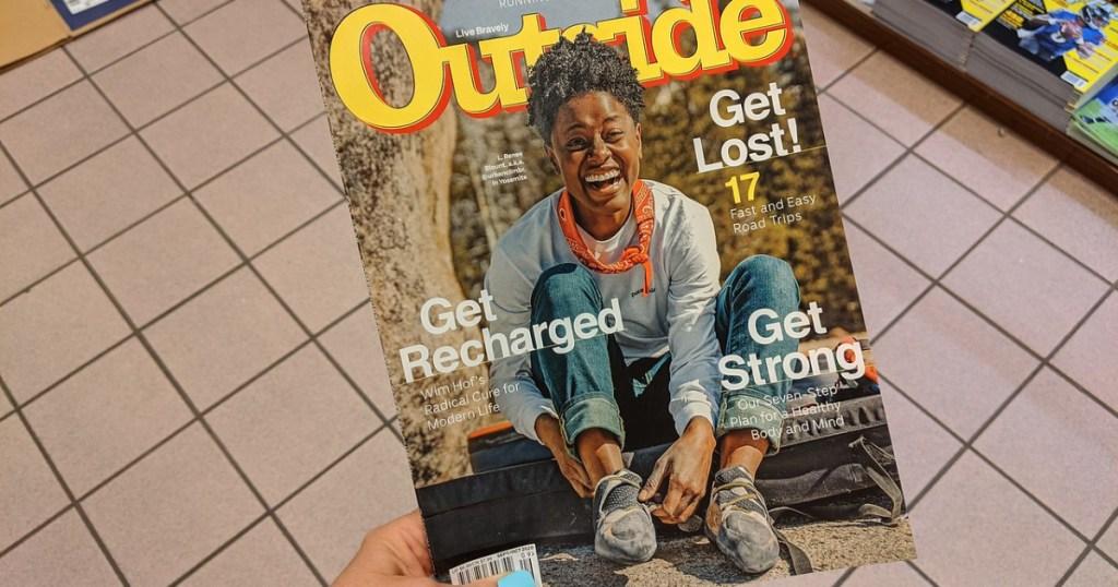 "hand holding magazine that says ""outside"""