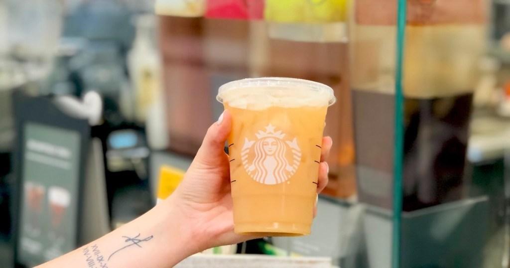 hand holding starbucks peach ring drink